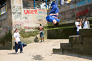 Young Parkour runners practice their moves on the river wall and steps down to the beach on the River Thames at the Southbank, London, UK. The soft landing area is ideal for acrobatics. The South Bank is a significant arts and entertainment district, and home to an endless list of activities for Londoners, visitors and tourists alike.