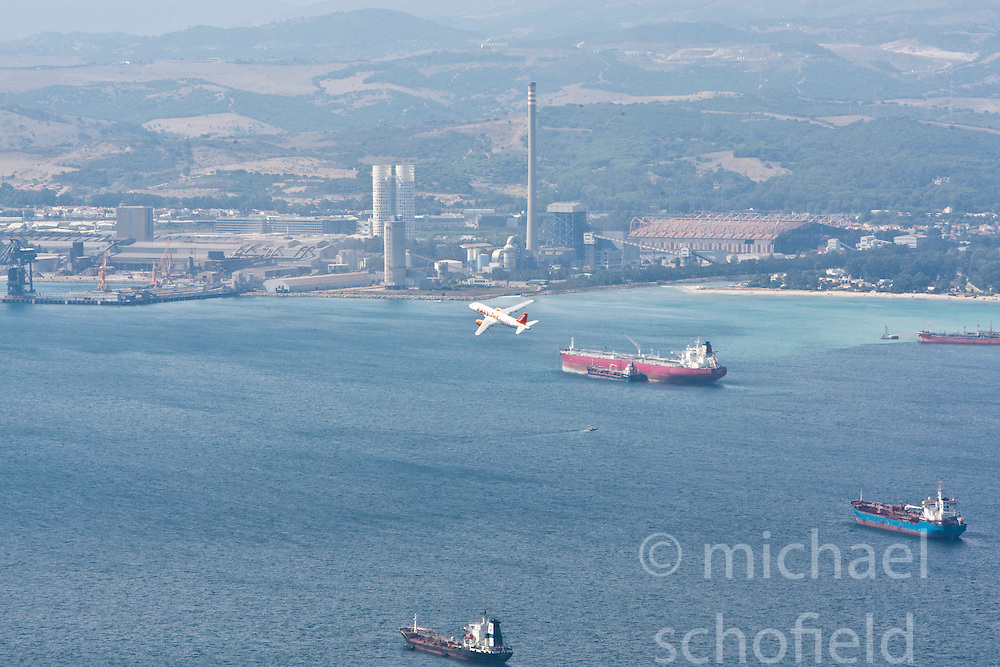 An EasyJet plane flies over the harbour of the Strait of Gibraltar. Photographs from the top of the Rock of Gibraltar. Images of Gibraltar, the British overseas territory located on the southern end of the Iberian Peninsula at the entrance of the Mediterranean.