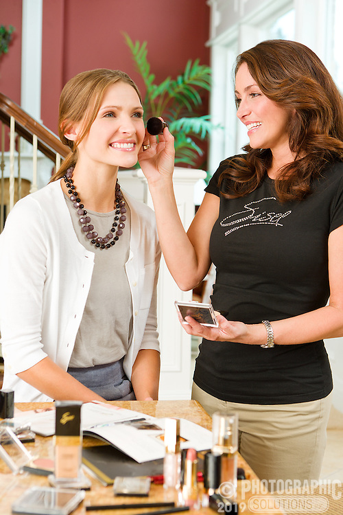 One woman applying make-up to another at a product party