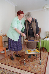 Carer assisting elderly woman with trolley,