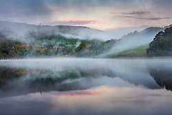 © Licensed to London News Pictures. 13/10/2020. Derwent UK. The morning mist & hills reflect into the calm water of Ladybower reservoir this morning in Derbyshire. Photo credit: Andrew McCaren/LNP