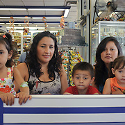 Genesis Acosta Lopez daughter of Merlin Lopez, Anderson Gimenez Lopez son of Mariela Lopez and Dana Gimenez Lopez daughter of Mariela Lopez, all from Honduras pose for a photograph after eating at La Espiguita Bakery, a Colombian place located in Brentwood. (July. 11, 2012)