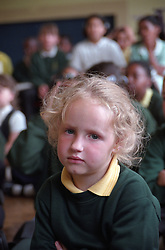 Portrait of primary school girl sitting on floor in school hall during assembly,