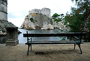 Park bench on beach, with view to Fortress Bokar (left)  and Fortress Lovrijenac (Fort of Saint Lawrence), guarding the entrance to Dubrovnik's oldest harbour, Kalarinja. Dubrovnik old town, Croatia