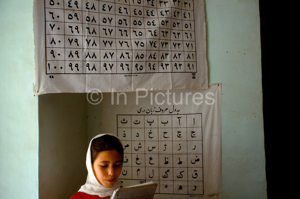 A girl learns to read in a classroom in Mazar-i-Sharif, Afghanistan. Traditionally, a girl's education was considered less important than boys - during the rule of the Taliban it was thought of as un-Islamic.