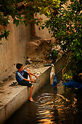 A young Moroccan boy cleans his sandals and feet in a small river that runs through the city of Fes, Morocco on Friday afternoon, June 08, 2007. (PHOTO BY TIMOTHY D. BURDICK)