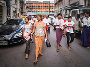 03 NOVEMBER 2015 - YANGON, MYANMAR:  NLD outreach workers walk down a Yangon street during a voter outreach program. Political parties are wrapping up their campaigns in Myanmar (Burma). National elections are scheduled for Sunday Nov. 8. The two principal parties are the National League for Democracy (NLD), the party of democracy icon and Nobel Peace Prize winner Aung San Suu Kyi, and the ruling Union Solidarity and Development Party (USDP), led by incumbent President Thein Sein. There are more than 30 parties campaigning for national and local offices.       PHOTO BY JACK KURTZ