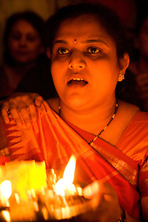 Woman worshipping by candlelight in celebration of Navratri; the Hindu festival of Nine Nights,