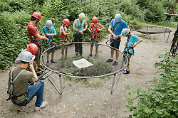 Young woman giving instruction to group of people for climbling crag