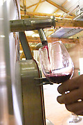 Chateau Grand Moulin. In Lezignan-Corbieres. Les Corbieres. Languedoc. Pouring a wine sample in a glass. Stainless steel fermentation and storage tanks. Tank spout. France. Europe.