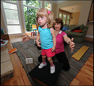 100607 - Smyrna -  Hannah Foy works on her balance under the watchful eye of Sharon Cook ,her physical therapist inside her home on Monday, June 7, 2010.  She is a special needs student at Nickajack Elementary School . Cobb County fired more than 170 special education teachers. It's a move that critics say will harm the most vulnerable students in the county. Of those laid off, 79 were part time. 72 were limited contract and 20 were full time.  They represent about 10 percent of the county's special ed. teachers.  Parents rallied around one pre-K teacher at Nickajack Elementary School who was cut, saying she is the reason their children can walk, talk and learn.<br /> © 2010 JOHNNY CRAWFORD