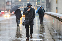 © Licensed to London News Pictures. 07/01/2016. London, UK. Commuters shelter themselves during a heavy rain on London Bridge in London on Thursday, 7 January 2016. Photo credit: Tolga Akmen/LNP
