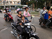 Mother and daughter traveling Cambodian style together on their motor bike. Its evening and rush hour with many heading home from work and school.