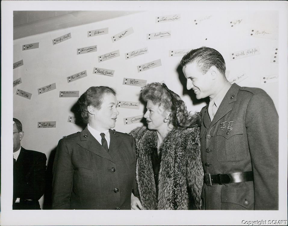 1944 Ginger Rogers and Lex Barker chat with a serviceman at he Hollywood Canteen