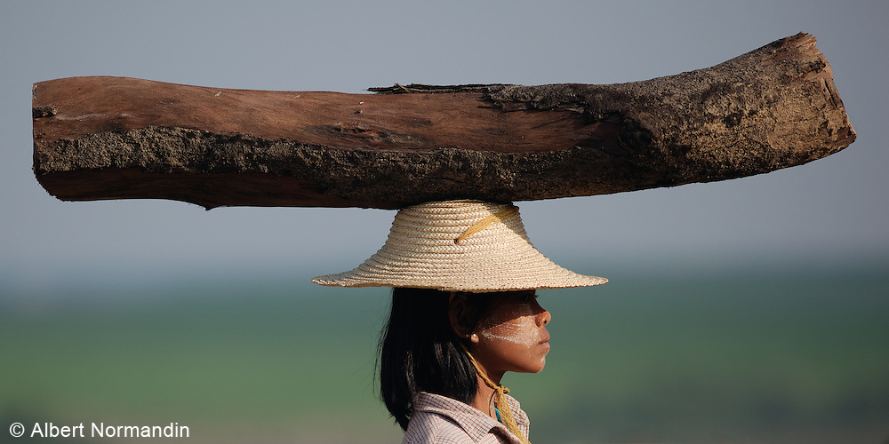 Young girl balances and carries long on her head