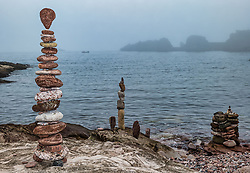 Dunbar, East Lothian, Scotland, UK, 9th July 2021. European Stone Stacking Championship: Competitors who have arrived for the weekend championship practise their skills on the beach on a very misty day. The event, which was cancelled last year, is part of the Edinburgh Science Festival. There will be several challenges including the most stones stacked in 20 minutes, the best balance from a given set of stones and an artistic challenge, as well as a children's event. This year, there is also an online part to the competition. Pictured: some of the stone stacks and sculptures on the beach in the mist.<br /> Sally Anderson | EdinburghElitemedia.co.uk