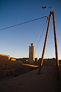 A modern light post stands overlooking the crumbling walls and mosque of Ait Bounou, an ancient kasbah, or fortified village, in the Moroccan Sahara. The town is quickly falling into ruin as the inhabitants flee the drying well and the advancement of the dunes expedited by a 16-year drought and the damming of the Draa River.