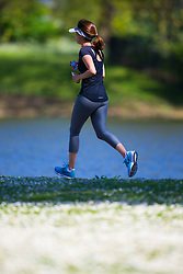 A woman runs past the boating lake on a perfect spring day in Regents Park. London, May 04 2018.