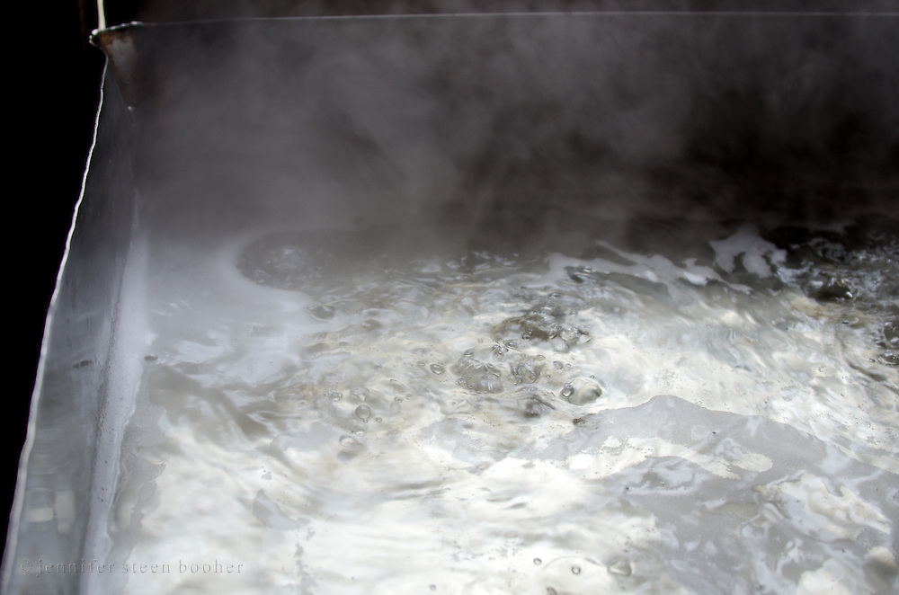 Closeup view of boiling maple sap as it slowly thickens into syrup.