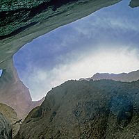 Mountaineer Sam Lightner (MR) descends a slot canyon below huge Shipton's Arch in the arid Kara Tagh Mountains near the Taklimakan Desert in China's Xinjiang province.