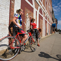 Two young women take a break from biking on Railroad Street in St. Johnsbury, Vermont.