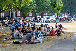 © Licensed to London News Pictures. 08/08/2020. London, UK. Members of the public enjoy a picnic and drinks on Richmond Green in South West London as temperatures reach to 35c for the second day in a row. Thousands of sun seekers have flocked to parks, rivers and the south coast as temperatures soar with beaches and roads becoming jammed with holidaymakers. The heat is set to continue for the rest of the week with temperatures expected reach over 30C. Photo credit: Alex Lentati/LNP