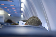 graying businessman reading his newspaper in an airplane