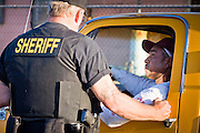 03 APRIL 2008 -- GUADALUPE, AZ:  An undercover deputy for the Maricopa County Sheriff's Department makes a traffic stop in Guadalupe during a sweep Thursday. The Maricopa County Sheriff's Department has started high profile zero tolerance crime sweeps targeting illegal immigrants but also arresting anyone they find breaking the law or with outstanding warrants. All of the previous sweeps have been in Phoenix city limits. This was the first one outside Phoenix, Guadalupe is a working class unincorporated town south of Phoenix. Most of the town's residents are Native Americans and Hispanics and hundreds of people lined the street to protest the sweep.   In 2011, the US Department of Justice issued a report highly critical of the Maricopa County Sheriff's Department and the jails. The DOJ said the Sheriff's Dept. engages in widespread discrimination against Latinos during traffic stops and immigration enforcement, violates the rights of Spanish speaking prisoners in the jails and retaliates against the Sheriff's political opponents.     PHOTO BY JACK KURTZ