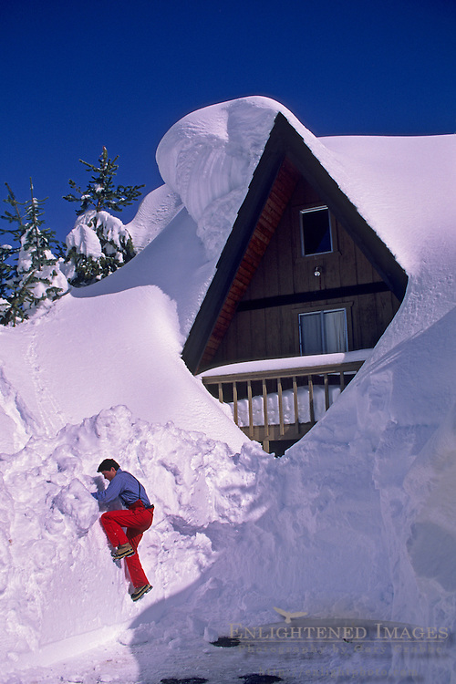 Climbing up a snow bank afer deep winter snow covers homes in Lake Tahoe, California