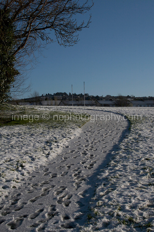 footprints on a path in snow covered Kilbogget Park in suburban in Dublin Ireland