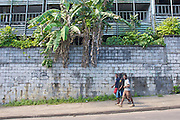 Three boys walk past a derelict building in Port Vila, Vanuatu.