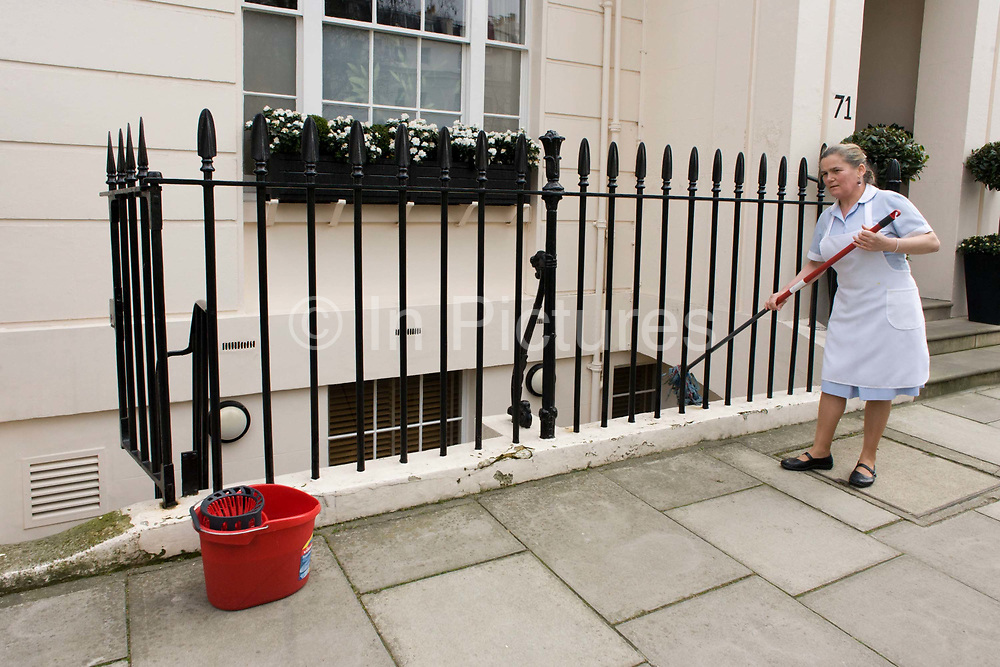 A maid uses a mop and bucket to wash down paintwork and railings at an exclusive address in Chester Square, Belgravia, SW1. In a house next door to where ex-Prime Minister Margaret Thatcher once lived from 1991 to 2012. The maid wearing an apron and regulation shoes uses her mop on a long handle to poke between the iron railings, wiping off dirst and dust. The paint however is peeling, needing redecoration and its cracks refilling. Chester Square was laid out between 1828 and 1840 by the 1st Duke of Westminster and his surveyor and architect Thomas Cundy II as part of the Grosvenor Estate.