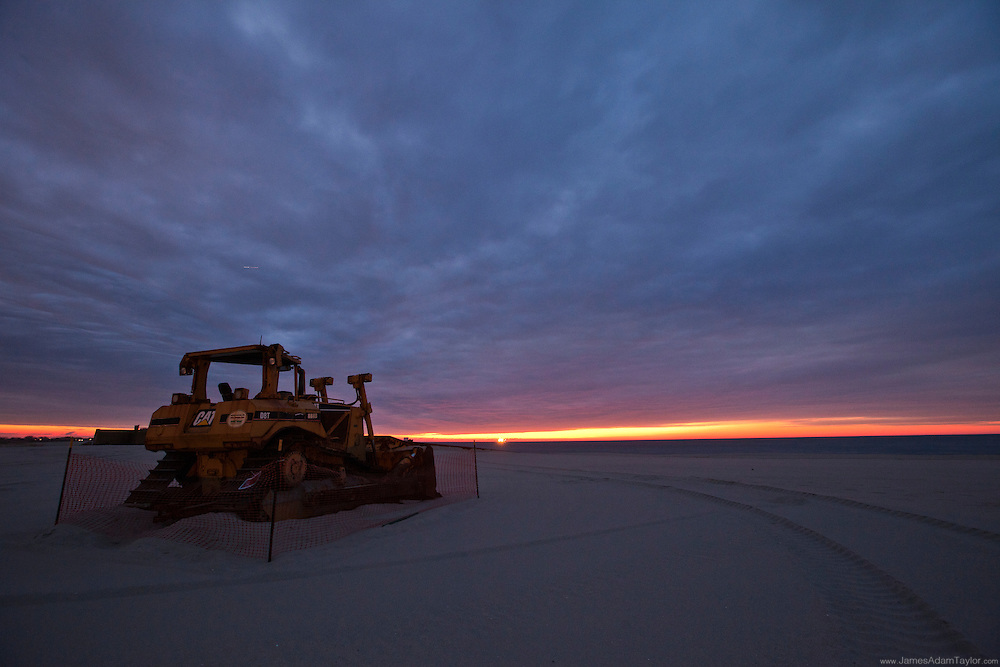 Sunrise over a bulldozer on the beach,  evidence of beach grooming, Cape May Point State Park.