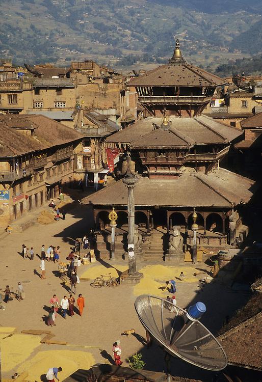 Asia, Nepal, Kathmandu Valley, Bhaktapur, Dattatraya Temple, satellite dish, and harvested rice in plaza
