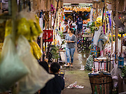 """11 AUGUST 2016 - BANGKOK, THAILAND:    A woman walks down an aisle in the flower section of Pak Khlong Talat in Bangkok. Pak Khlong Talat (literally """"the market at the mouth of the canal"""") is the best known flower market in Thailand. It is the largest flower market in Bangkok. Most of the shop owners in the market sell wholesale to florist shops in Bangkok or to vendors who sell flower garlands, lotus buds and other floral supplies at the entrances to temples throughout Bangkok. There is also a fruit and produce market which specializes in fresh vegetables and fruit on the site. It is one of Bangkok's busiest markets and has become a popular tourist attraction.        PHOTO BY JACK KURTZ"""