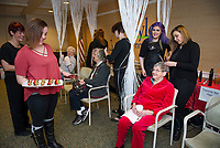 """Felicia Morasse from Empire Beauty School offers chocolate covered strawberries to their guest Connie Wisse as she gets her hair set by Stephani Kendrick and Cory Navoy during Taylor Home's """"Spa Day"""" on Wednesday morning.  (Karen Bobotas/for the Laconia Daily Sun)"""