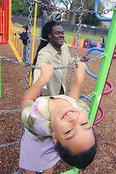 Single father and young daughter playing on equipment in playground,