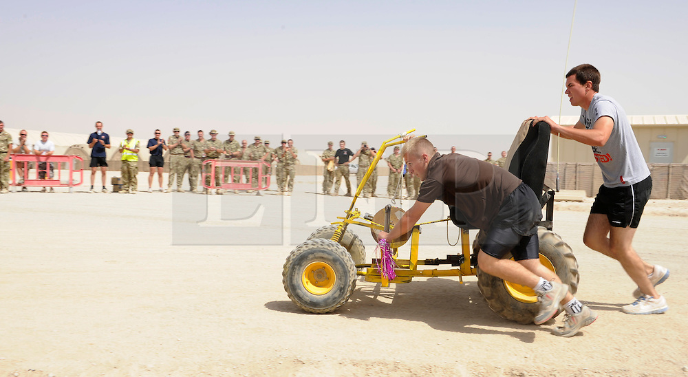 © Licensed to London News Pictures. 18/08/2011. Bastion, Afghanistan. A group of soldiers from the Royal Engineers push their home made kart after finishing last in a 'make your own' Kart race at Camp Bastion.  The race was organised to raise money for Kart Force, a UK based charity that modifies go karts so that they can be used by amputees and injured soldiers.  Photo credit : Sergeant Alison Baskerville/LNP