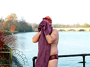 A member of the Serpentine Swimming Club drying off with a purple towel after swimming in the Serpentine Lake, Hyde Park, London, UK. The Serpentine Lake is situated in Hyde Park, London's largest central open space. The Serpentine Swimming Club was formed in 1864 'to promote the healthful habit of bathing in open water throughout the year'.  Its headquarters were beneath an old elm tree on the south side of the lake, a wooden bench for clothing being the only facility.  At this time London was undergoing rapid expansion and Hyde Park was now in the centre of a densely populated built up area and provided a place of relaxation to its urbanised masses. Now, the club has its own (somewhat spartan) changing facilities and members are  permitted by the Royal Parks to swim in the lake any morning before 09:30.  They race every Saturday morning throughout the year, regardless of the weather.