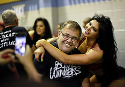 12 March 2016. Metairie, Louisiana.<br /> Wrestling action from Wildkat Sports and Entertainment's 'March into Mayhem' at the Meisler Middle School. Wrestler Katie Forbes poses with a happy fan during the half time break. <br /> Photo©; Charlie Varley/varleypix.com
