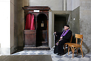 elderly priest sitting and waiting by his confessional, Duomo, Città di Castello, Umbria, Italy