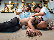"""14 MARCH 2014 - NAKHON CHAI SI, NAKHON PATHOM, THAILAND:  An archan gives a man a sak yant tattoo at Wat Bang Phra. Wat Bang Phra is the best known """"Sak Yant"""" tattoo temple in Thailand. It's located in Nakhon Pathom province, about 40 miles from Bangkok. The tattoos are given with hollow stainless steel needles and are thought to possess magical powers of protection. The tattoos, which are given by Buddhist monks, are popular with soldiers, policeman and gangsters, people who generally live in harm's way. The tattoo must be activated to remain powerful and the annual Wai Khru Ceremony (tattoo festival) at the temple draws thousands of devotees who come to the temple to activate or renew the tattoos. People go into trance like states and then assume the personality of their tattoo, so people with tiger tattoos assume the personality of a tiger, people with monkey tattoos take on the personality of a monkey and so on. In recent years the tattoo festival has become popular with tourists who make the trip to Nakorn Pathom province to see a side of """"exotic"""" Thailand.  PHOTO BY JACK KURTZ"""