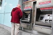 Israel, Tel Aviv, Allenby street, Man withdraws money from an ATM (Automatic Teller Machine)