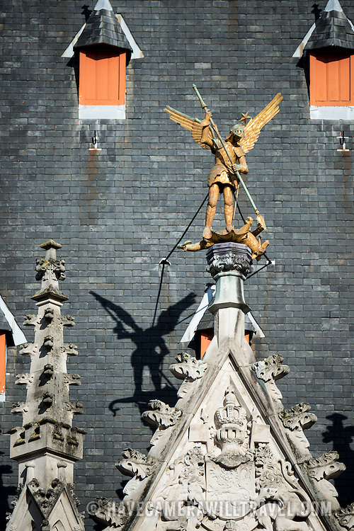 A statue of the Archangel St Michael slaying a dragon on the roof of the Provincial Court building in the Markt (Market Square) in the historic center of Bruges, a UNESCO World Heritage site.
