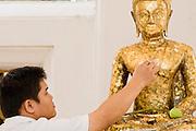 02 MARCH 2008 -- BANGKOK, THAILAND: A man rubs gold leaf on a Buddha statue at Wat Arun (Temple of the Dawn) in Bangkok, Thailand.     Photo by Jack Kurtz