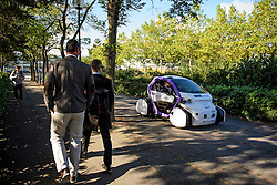 © London News Pictures. 11/10/2016. Milton Keynes, UK. Pedestrians watch a driverless car being tested around pedestrian areas in Milton Keynes in the first public test of autonomous electric vehicles in the UK. The vehicles have been developed by the Oxford Robotics Institute and Oxbotica. Photo credit: Ben Cawthra/LNP