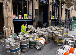 Man restocking pub with beer barrels in Edinburgh Old Town, Scotland, UK