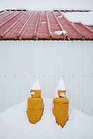Yellow propane gas tanks by a shed in snow. Red roof. South Iceland.