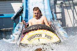 © Licensed to London News Pictures. 30/06/2016. Brighton, UK. Members of the public take a ride on the Big Splash water attraction on the Brighton Palace Pier as thousands of visitors take to the beach in Brighton and Hove as sunny and hot weather is hitting the seaside resort. Photo credit: Hugo Michiels/LNP