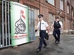 © Licensed to London News Pictures. 19/09/2018. London, UK. Police pass the entrance to The Hussaini Association Islamic Centre in Cricklewood, north London where a car hit two pedestrians last night. The incident , which took place in the early hours of this morning outside the centre, is being treated as a possible hate crime. Police are looking for a male driver who failed to stop at the scene, as well as two men and one woman in the car, all in their 20s. Photo credit: Peter Macdiarmid/LNP